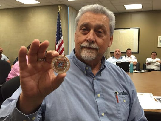 Department Director Dale Jones holds the coin at the