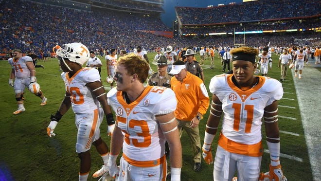 Vols coach Butch Jones, center, leaves the field with players after Tennessee's 28-27 loss to Florida at Ben Hill Griffin Stadium in Gainesville, Fla., on Sept. 26, 2015.