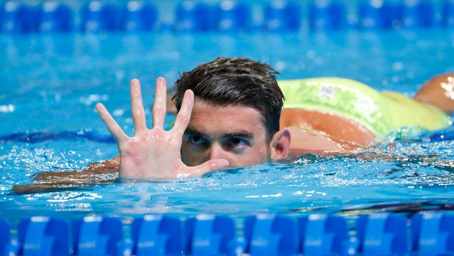 Michael Phelps holds up five fingers during the finals for the men's 200 meter butterfly in the U.S. Olympic swimming team trials at CenturyLink Center.