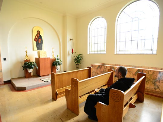 Brother Andre Love, a Benedictine monk, sits in the church after praying at the Mount Angel Abbey. Love is curator of the Abbey's art collection.
