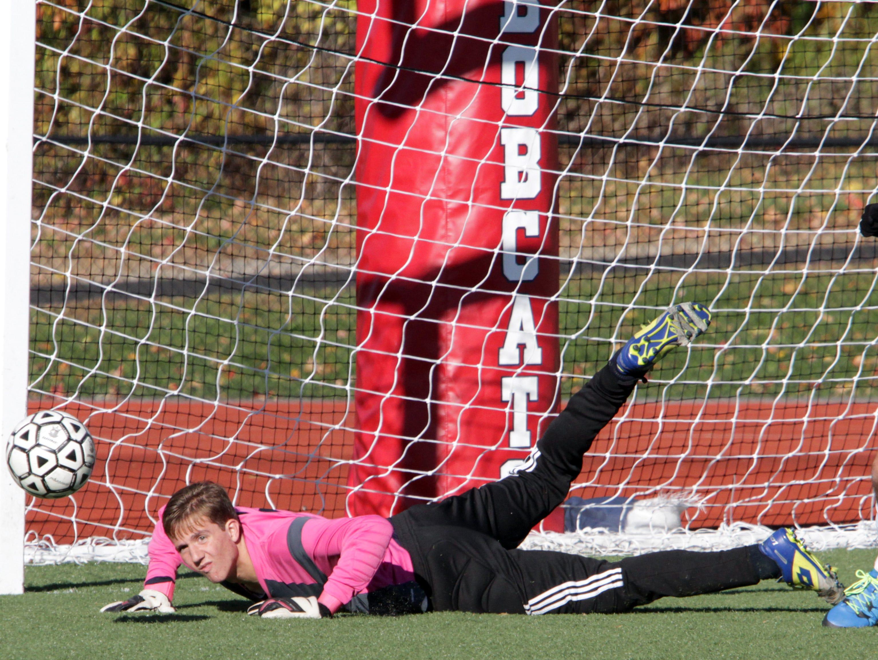 Pelham's goalie Matthew O'Neil dives for a wide shot kicked by Byram Hills' Garrett Wolfe during their boys soccer quarterfinal Class A game at Byram Hoills High School in Armonk Oct. 26, 2015.