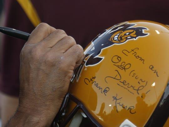 ASU head coach Herm Edwards signs an ASU helmet.