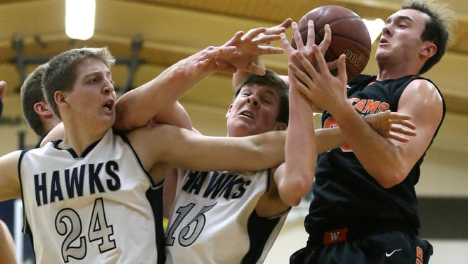 Xavier's Matt DeYoung (24) and Nate DeYoung (15) fight for a rebound against West De Pere's Joe Janus during Tuesday's game at Xavier.