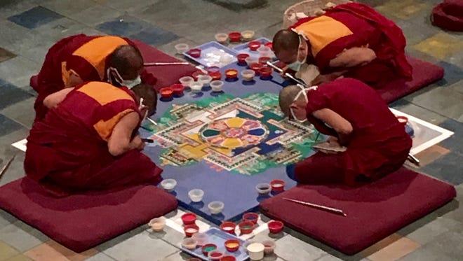 Drepung Gomang monks work on creating their sand mandala at the Festival of Faiths.