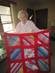 Betty shows off a small red blanket she has for sale
