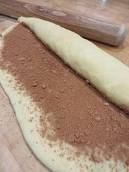 The dough is sprinkled with filling and rolled up.