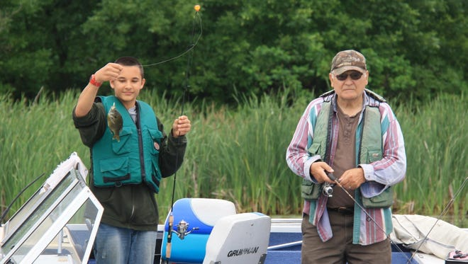 "Volunteer Marvin Mastey is shown with a young angler at a ""Hooked on Fishing"" event."