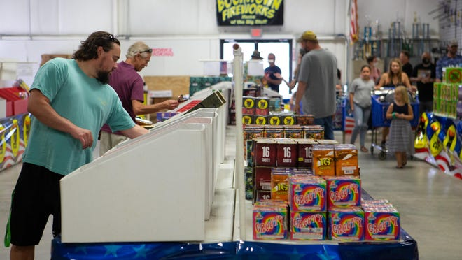 Customers look over rows of fireworks Friday at Boomtown Fireworks, 5007 S.W. Topeka Blvd.