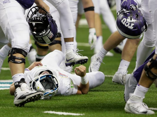 TCU players storm the field after their win as Oregon quarterback Jeff Lockie lies on the turf after he was injured on the final play of the game, in the third overtime, in the Alamo Bowl NCAA college football game, Saturday, Jan. 2, 2016, in San Antonio. TCU won 47-41. (AP Photo/Austin Gay)