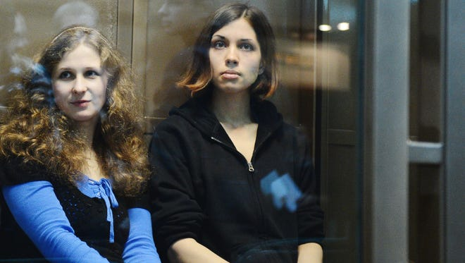 Pussy Riot members Nadya Tolokonnikova and Maria Alekhina sit in a glass-walled cage in a court in Moscow on Oct. 10, 2012.