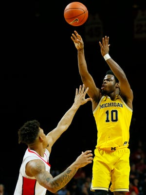Feb 22, 2017; Piscataway, NJ, USA; Michigan Wolverines guard Derrick Walton Jr. shoots over Rutgers Scarlet Knights guard Corey Sanders during the first half at Louis Brown Athletic Center.