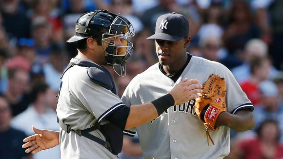 \New York Yankees' Austin Romine, left, talks with Luis Severino during the sixth inning of a baseball game against the Boston Red Sox in Boston, Saturday, Sept. 17, 2016.