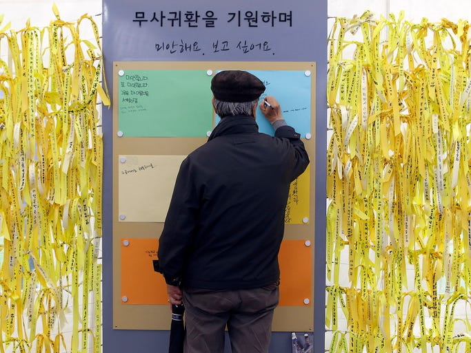 A man writes a message for missing passengers aboard the sunken ferry Sewol at a memorial altar in front of the City Hall in Seoul. The ferry capsized and sank on April 16.
