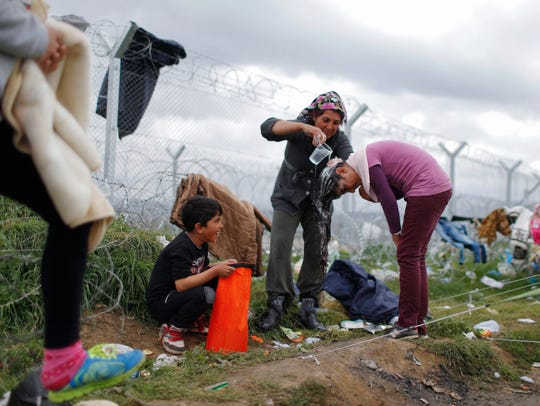 A girl has her hair washed between tents at the Greek-Macedonian