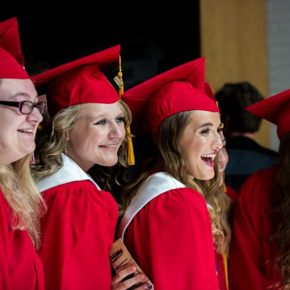 Graduates take photos while getting ready to line up
