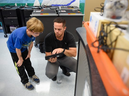 Jason Menth, technology integrationist, gets fourth-grader Donald Conrad started with a robot Thursday, Sept. 14, at Talahi Community School.
