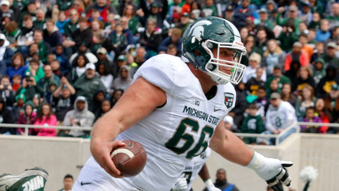 Michigan State offensive lineman Jack Allen scores a rushing touchdown during the Spartans' spring game, Saturday, April 25, 2015, in East Lansing.