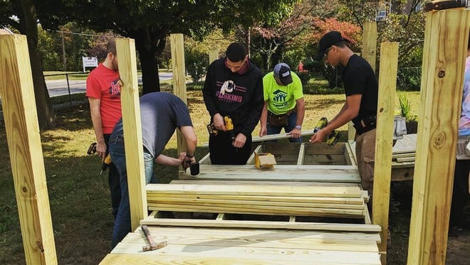 Members of ASPIRA YouthBuild and Cumberland County Habitat for Humanity volunteers work together to build a ramp in Vineland.