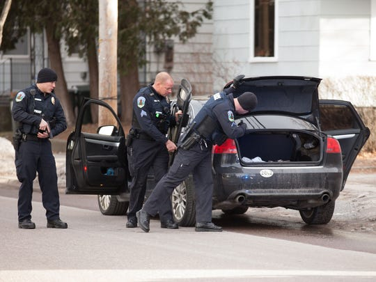 Police with guns drawn search a car in January 2015