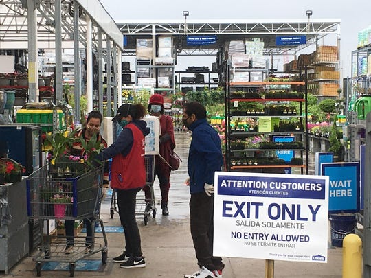 Customers get checked out from the garden center at a Lowe's store in Harrisburg, Pa., Wednesday, May 6, 2020. As swaths of Pennsylvania prepare for a limited reopening Friday, some fed-up business owners are jumping the gun and have resumed serving customers in defiance of Gov. Tom Wolf's shutdown order. (AP Photo/Mark Scolforo)