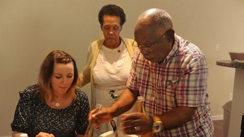 Andrea Prince, elder specialist for Catholic Charities of Tennessee, is served a traditional Ethiopian meal by Asfaw Hubtewold, 84, and his wife, Zewudnesh Tesema, 68.