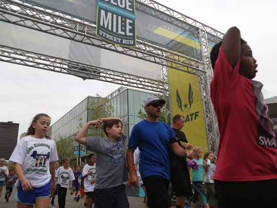 Elementary school students cross the finish line of the Iowa Kidstrong Fun Run during the Grand Blue Mile on Tuesday, April 25, 2017, in downtown Des Moines.