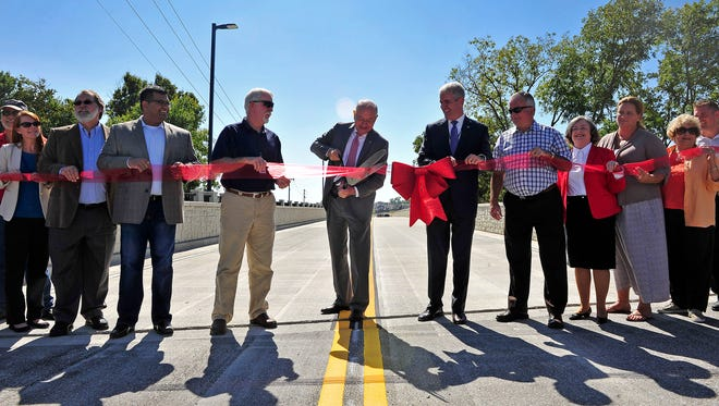 Mayor Ken Moore cuts the ribbon at the opening ceremony of a long-awaited Carothers extension in Franklin, Tenn., Wednesday, Sept. 23, 2015.