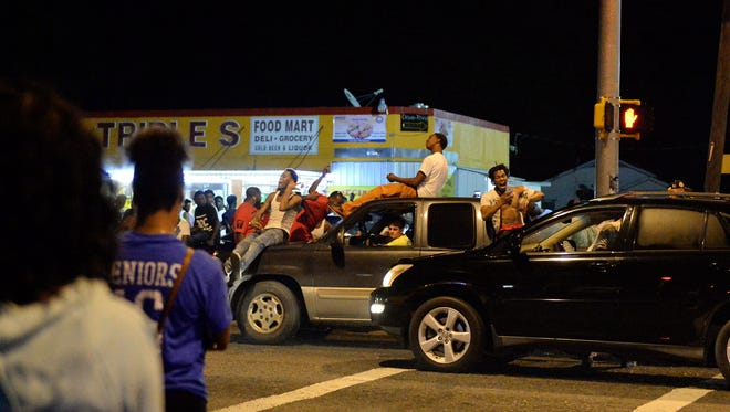 Protesters gather near the Triple S Food Mart, the area where Alton Sterling was shot and killed by Baton Rouge Police in the early hours of Tuesday morning, July 5, 2016, in Baton Rouge, La.