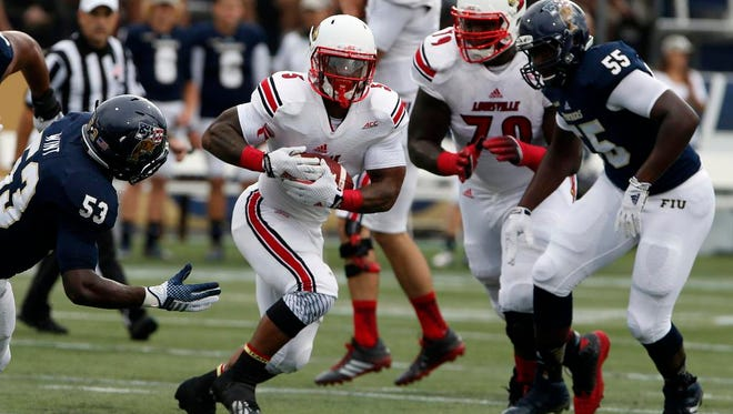 Sep 20, 2014; Miami, FL, USA; Louisville Cardinals running back Michael Dyer runs the ball between FIU Golden Panthers linebacker Anthony Wint (53) and defensive end Michael Wakefield (55) in the first quarter at FIU Stadium. Mandatory Credit: Robert Mayer-USA TODAY Sports