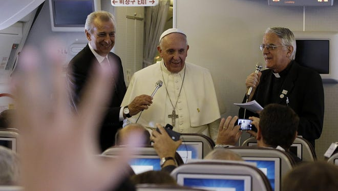 Pope Francis, second from left standing, meets the media during an airborne press conference on his journey back to Rome from Seoul, South Korea, Aug. 18, 2014.
