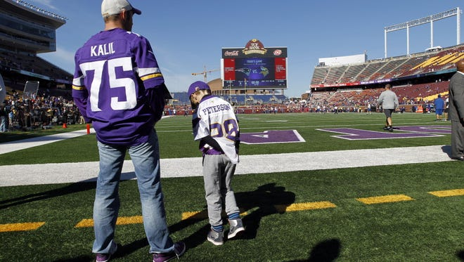 A boy wears an Adrian Peterson jersey before the start of an NFL football game Sunday in Minneapolis.