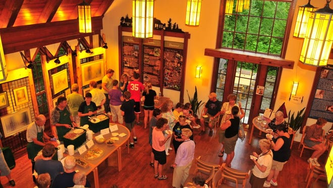 Guests mingle in the Jens Jensen Visitor Center at an old-fashioned ice cream social at The Clearing Folk School in Ellison Bay in 2013.
