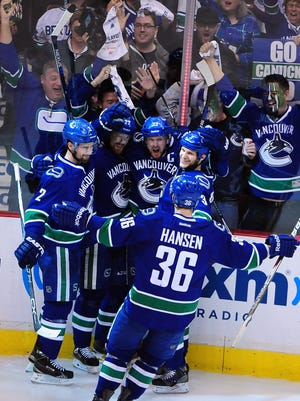 Vancouver Canucks forward Daniel Sedin (22) celebrates with forward Henrik Sedin (33) and defenseman Dan Hamhuis (2) and forward Jannik Hansen (36) and defenseman Kevin Bieksa (3) after scoring against Calgary Flames during the third period of Game 5.