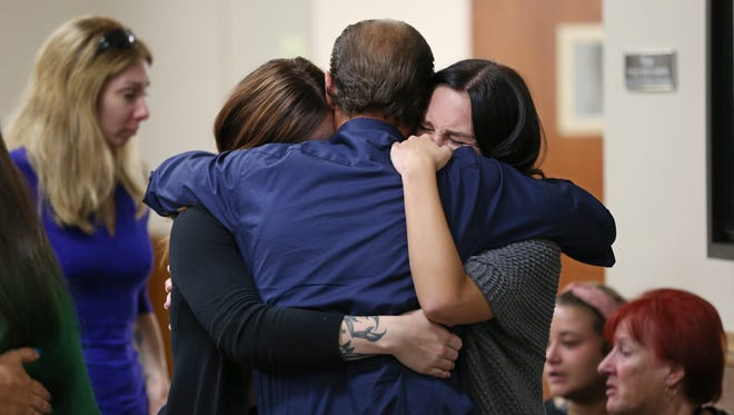 John Geer, center, grandfather of Brook Stagles, hugs family members outside court following the guilty verdict of Erica Bell.