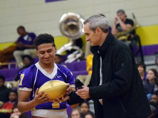 Chance Murphy (left), an Alexandria Senior High School football player, looks at a gold football handed to him by Chris Boniol (right), former kicker for the Dallas Cowboys and 1990 Alexandria Senior High School alum. The NFL is honoring high schools who've had alumni play in the Super Bowl with gold football. The event is being done in celebration of the 50th anniversary of the Super Bowl.