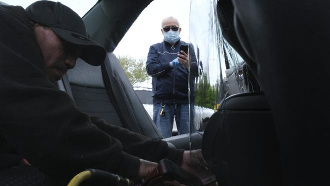 In this  May 6, 2020, file photo, Luis Hidalgo, wearing face mask, watches as Joel Rios installs a plastic barrier in his car to protect himself and his passengers from the new coronavirus in the Bronx borough of New York. Mask slackers will now have to provide photographic proof they're wearing a face covering before boarding an Uber. The San Francisco-based company unveiled a new policy Tuesday, Sept. 1, stipulating that if a driver reports to Uber that a rider wasn't wearing a mask, the rider will have to take a selfie with one strapped on the next time they summon a driver on the world's largest ride-hailing service.