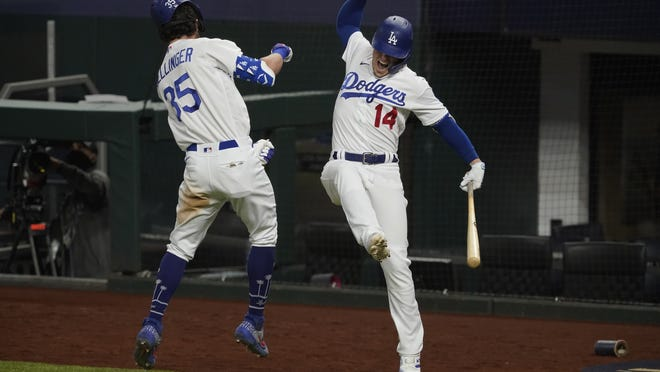 Los Angeles's Cody Bellinger celebrates his home run with Enrique Hernandez against the Atlanta Braves during the seventh inning in Game 7 on Sunday.