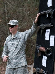 """Sgt.1st. Class Chris Shortt gives a class on common weapons used by the """"bad guys"""" to a group of VIPs visiting Camp Rudder at Eglin Air Force Base."""