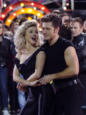 """This image released by Fox, Juliane Hough and Aaron Tveit appear during a performance of """"Grease: Live."""" With this hectic, ambitious and hormonal """"Grease,"""" Fox proved it could up the ante in the new mini-industry of musicals on TV, an industry so far controlled by NBC, with its """"The Sound of Music Live!"""" ''Peter Pan Live!"""" and """"The Wiz Live."""" (Frank Micelotta/FOX via AP)"""