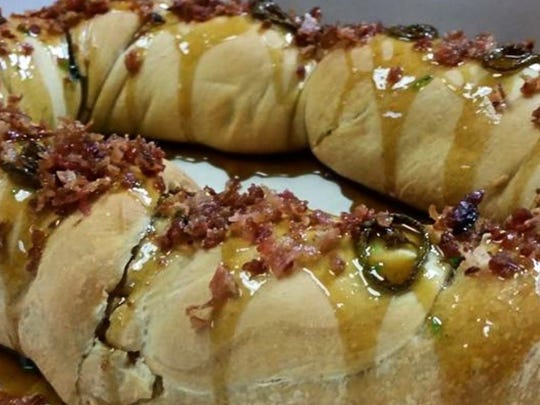 Cajun Market Donut Company's boudin king cake is topped with cane syrup, pepper jelly and bacon.