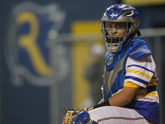 Rickards catcher Jayden Figueroa looks for a call from the dugout.