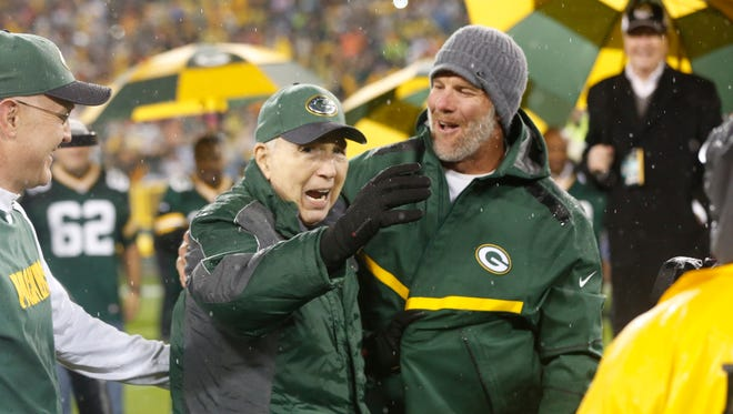 Brett Favre smiles with Bart Starr during a ceremony at halftime of an NFL football game between the Green Bay Packers and Chicago Bears Thursday, Nov. 26, 2015, in Green Bay, Wis. Favre's retired No. 4 and name were unveiled inside Lambeau Field during the ceremony.