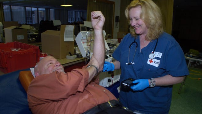 Farmington Hills mayor Ken Massey has been donating blood since he was 16 years old. Here RN Lynn Gagin lets him know he can get up and have an orange juice.