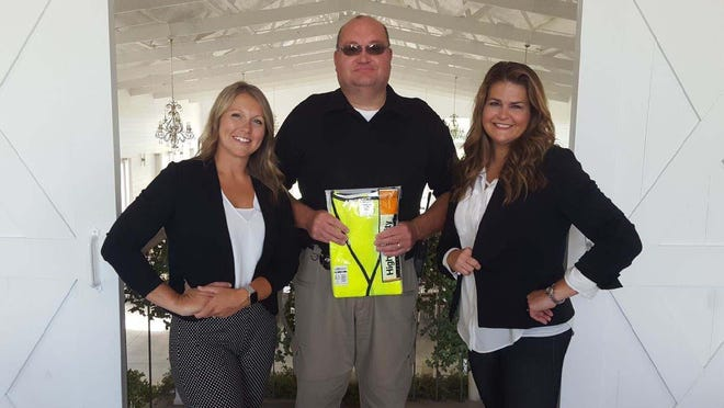 Chirsty Potts and Lindsey Higgins from The Barn at Fairview Acres flank Henderson County Sheriff Donald Seitz, center, as he holds a safety vest purchased with money donated by Potts and Higgins.