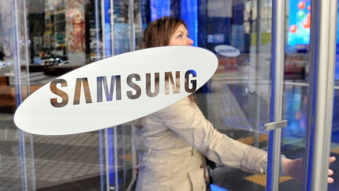 A visitor walks past a logo of Samsung Electronics at the company's headquarters in Seoul on November 22, 2013.