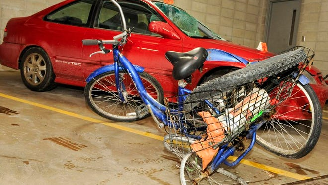 This Jan. 21, 2014, photo shows Steven Gove's three-wheeled tricycle and the car that hit him Saturday night at the Manitowoc, Wis., police station. .