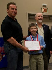 Jacob Littler receives a scholarship certificate from Arnold Schwarzenegger after being named one of the top male athletes at the 2015 Arnold Sports Festival earlier this month in Columbus.