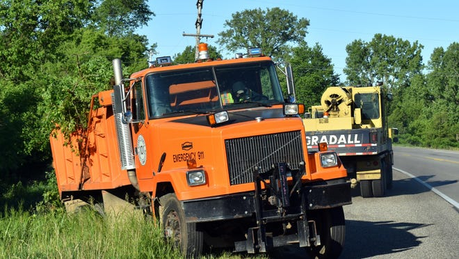 Road commission crews clear away dozens of trees and limbs on state and county roads after a June 10 storm.
