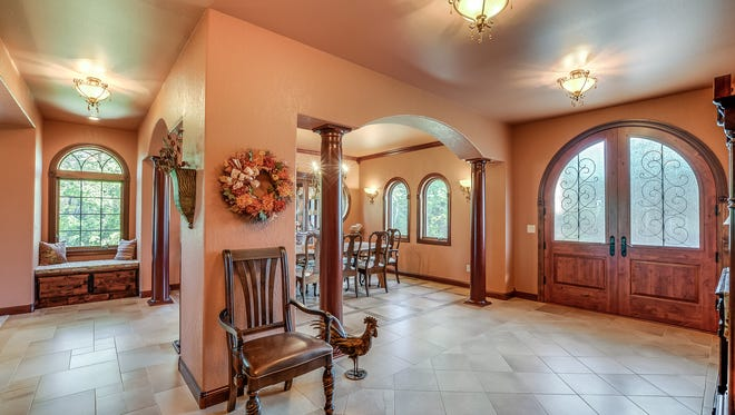 The home's wide rounded double doors welcomes visitors to a spacious main area.