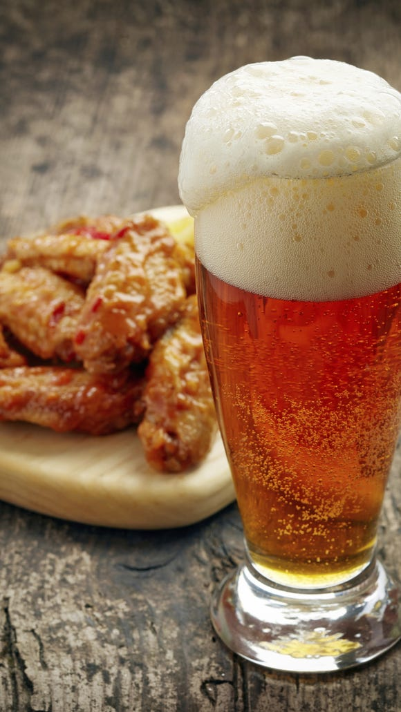 A gass of fresh beer and fried chicken wings